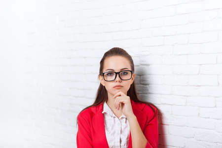 ponder: Businesswoman serious wear red jacket glasses hold chin ponder business woman over office wall