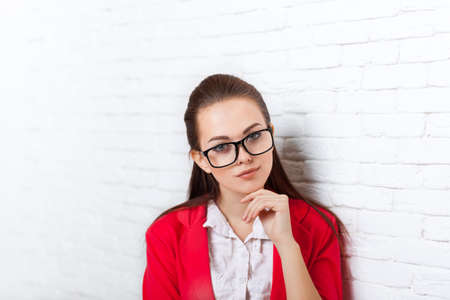 to ponder: Businesswoman serious wear red jacket glasses hold chin ponder business woman smile over office wall