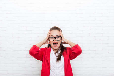 head wear: Excited businesswoman happy smile hold head wear red jacket glasses business woman over office wall