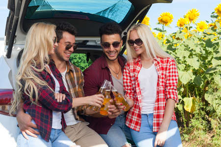 clink: Friends drinking beer toasting clink bottles sitting in car trunk outdoor countryside, happy smile people group summer sunflower field