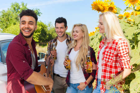 guy playing guitar: Young people listening guy playing guitar friends drinking beer bottles outdoor countryside, two couple standing near car happy smile summer sunflower Stock Photo