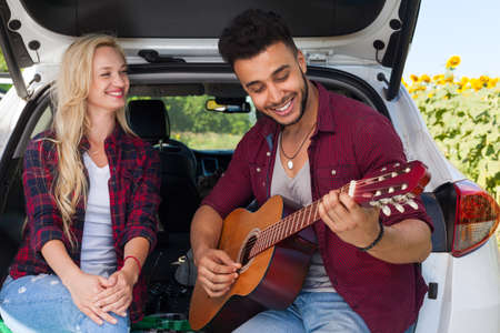 car trunk: Young girl listening boyfriend playing guitar couple sitting car trunk outdoor countryside, happy smile summer day