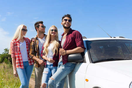 automobiles: People group looking side copy space blue sky standing near car outdoor countryside two couple summer day holiday trip