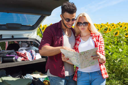 mix race: Couple looking road map standing sunflowers field outdoor, mix race man and woman standing near car trunk summer day holiday trip