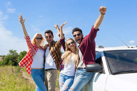 day trip: People group outdoor countryside excited raise arms friends smile holding hands up near car summer day trip Stock Photo