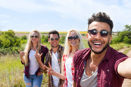 smile close up: Man hold smart phone camera taking selfie photo friends face smile close up countryside young people group outdoor two couple summer sunny day