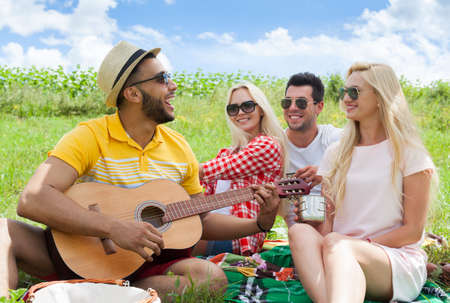 guy playing guitar: Young people listening guy playing guitar group friends summer day sitting green grass outdoor picnic nature two couple men with girls laugh singing song together