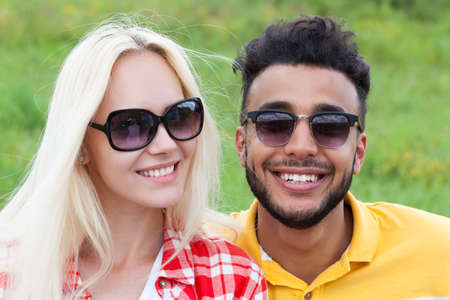 Couple face close up outdoor green grass, mix race man and woman sunglasses happy smile embrace summer day Stock Photo