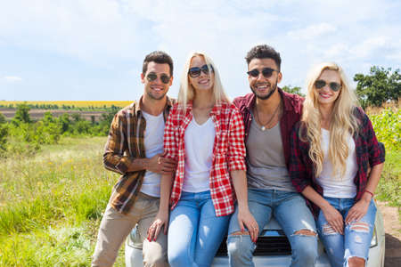 day trip: Friends sitting on car outdoor countryside people smile summer day trip Stock Photo