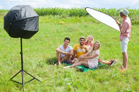 People outdoor shooting set up during photo session, Friends picnic sitting blanket green grass two couple summer sunny day blue sky, photographer assistant hold sunlight diffuser