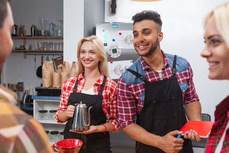 mix race: Barista serving clients give cup tea coffee shop bar counter, mix race man and woman happy smile to customer Stock Photo
