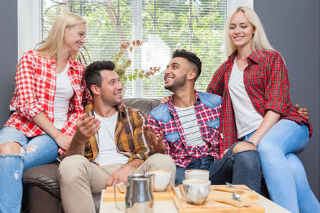 mix race: Young people drink coffee shop, friends sitting table smiling two couple mix race men women talking