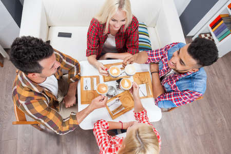 mix race: Young people drink coffee shop, friends sitting table smiling two couple mix race men women talking top angle above view Stock Photo