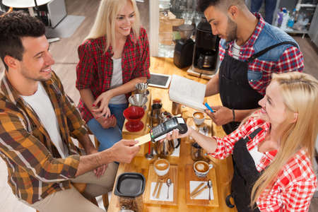 mix race: Barista serving clients give cup coffee shop bar counter, mix race man and woman happy smile to customer top angle above view