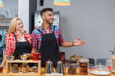 mix race: Barista coffee shop owner couple happy smile welcome at bar counter mix race man woman small business