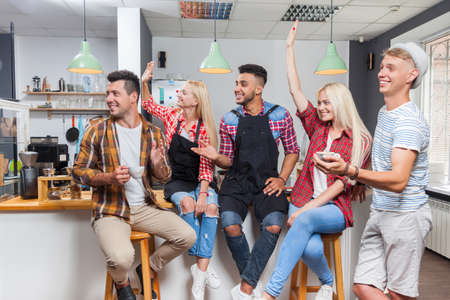 mix race: People friends drinking coffee shop talking laughing with barista sitting at bar counter, mix race man and woman happy smile wave hands raised up Stock Photo