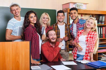 Student High School Group lachend met Professor zit aan Bureau, lachende jonge mensen Universiteit klas over schoolbord Stockfoto