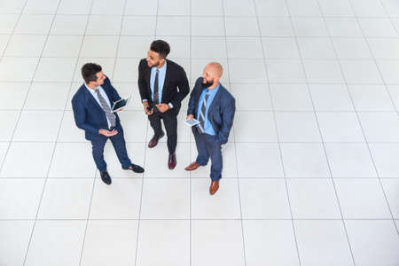 businessman suit: Business Man Group Discussion Meeting, Three Businessman Talking Hold Tablet Computer, Businesspeople Colleague Team Top Angle View Stock Photo