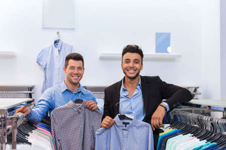 mix race: Two Handsome Business Man Fashion Shop, Happy Smiling Mix Race Friends Customers Choosing Clothes Shirts In Retail Store Young People Shopping Formal Wear