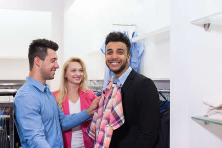 customer tailor: Young People Shopping, Happy Smiling Friends Two Couple Customers In Fashion Shop Fitting Shirt Choosing Clothes Shirts