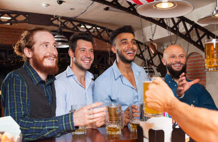 mix race: Man Group In Bar Hold Beer Glasses, Standing At Counter Order Barman, Mix Race Cheerful Friends Meeting Pub Communication