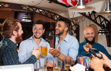 barmen: Man Group In Bar Drinking Beer, Mix Race Friends Meeting, Bearded Man Pay With Credit Card To Barmen Standing At Counter Stock Photo