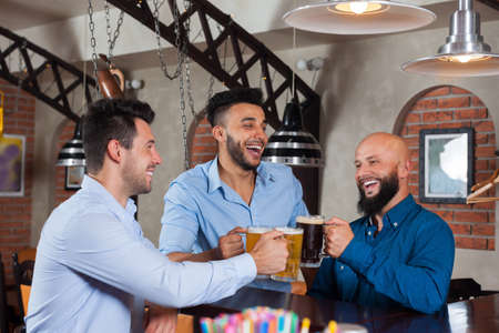 mix race: Three Man In Bar Clink Glasses Toasting, Drinking Beer Hold Mugs, Mix Race Cheerful Friends Wear Shirts Meeting Pub Communicate Talking