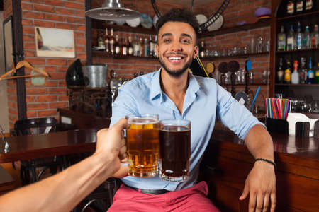 clink: Hispanic Man In Bar Clink Glasses Toasting, Drinking Beer Hold Mugs, Cheerful Friends Meeting Pub Communicate Talking Stock Photo