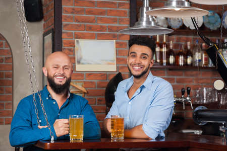 mix race: Two Mix Race Man In Bar Hold Glasses Sit At Counter, Drinking Beer, Cheerful Friends Meeting Pub Communicate Talking Stock Photo