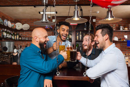 mix race: Man Group In Bar Clink Glasses Toasting, Drinking Beer Hold Mugs, Mix Race Cheerful Friends Wear Shirts Meeting Pub Communicate Talking