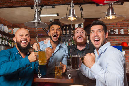 mix race: Man Group In Bar Screaming And Watching Football, Drinking Beer Hold Mugs, Mix Race Cheerful Friends Wear Shirts Meeting Pub Communicate Stock Photo