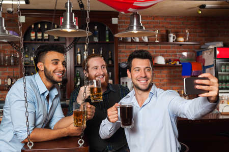 mix race: Man Group In Bar Taking Selfie Photo, Drinking Beer, Mix Race Cheerful Friends Meeting Communication, Guy Hold Smart Phone