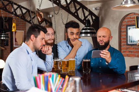 mix race: Man Group In Bar Drinking Beer, Frustrated Guy Hold Cell Smart Phone, Mix Race Friends Upset Serious Looking