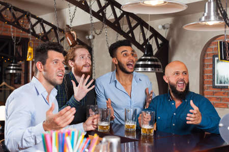mix race: Man Group In Bar Drinking Beer, Mix Race Frustrated Friends Screaming And Watching Football, Upset Serious Looking