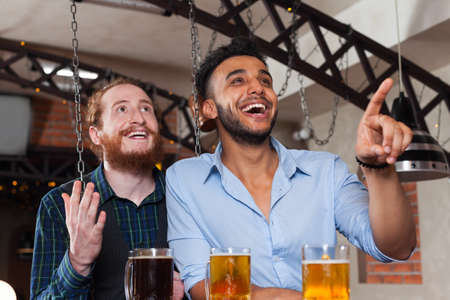 mix race: Two Man In Bar Watching Football, Drinking Beer Standing At Counter Point Finger, Mix Race Cheerful Friends Meeting Pub Communicate