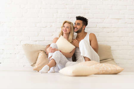 Young Couple Sit On Pillows, Happy Smile Hispanic Man And Woman Hug Lovers In Bedroom Over White Brick Wall