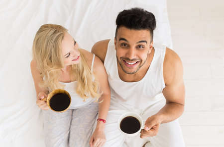 Young Couple Drink Coffee Sitting In Bed, Happy Smile Young Hispanic Man And Woman Top Angle View Lovers Hold Cups Bedroom
