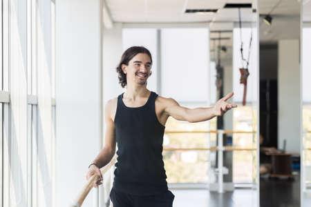 ballet hombres: Masculino joven bailarín de ballet Presenta Cerca Barre, hombre que practica en estudio de la danza