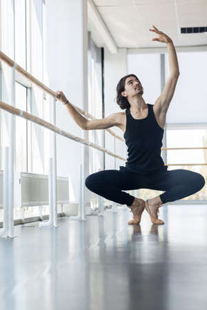 male ballet: Young Male Ballet Dancer Posing Near Barre, Man Practicing In Dance Studio