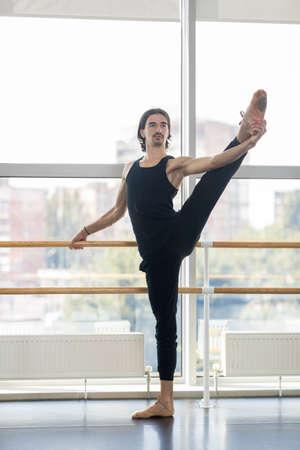 ballet hombres: Masculino joven bailarín de ballet Presenta Cerca Barre, practicante del hombre estiramiento en estudio de la danza