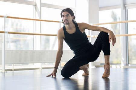 ballet hombres: Masculino de los jóvenes del ballet del bailarín, hombre practicando estiramiento en estudio de la danza