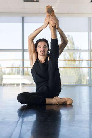 ballet hombres: Masculino joven bailarín de ballet se sienta en suelo de estiramiento, el hombre que practica en estudio de la danza Foto de archivo