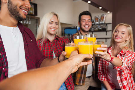mix race: People Friends Drinking Orange Juice, Toasting At Bar Counter, Mix Race Man And Woman Cheers Happy Smiling Stock Photo