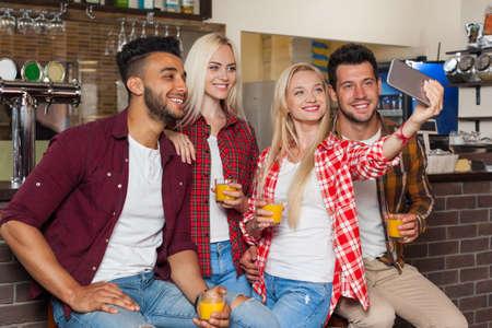 mix race: People Friends Taking Selfie Photo Drinking Orange Juice, Sitting At Bar Counter, Mix Race Man Woman Hold Smart Phone Happy Smile Communication