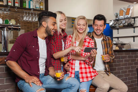 mix race: People Friends Using Cell Smart Phone, Drinking Orange Juice Talking Laughing Sitting At Bar Counter, Mix Race Man And Woman Happy Smile Communication Stock Photo