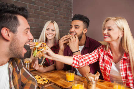 eating fast food: People Group Eating Fast Food Burgers Sitting At Wooden Table In Cafe, Friends Meeting Communication Stock Photo