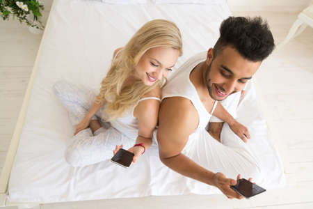 66127820-young-couple-sitting-in-bed-hap