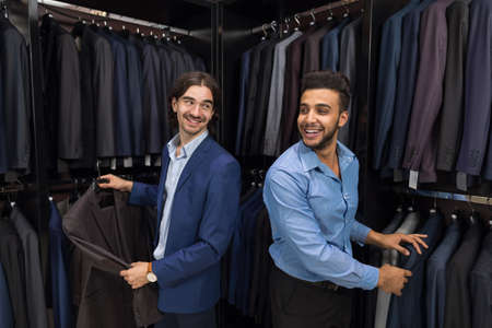 customer tailor: Handsome Business Man Fashion Shop, Customers Choosing Suit Clothes In Retail Store Young People Shopping Formal Wear