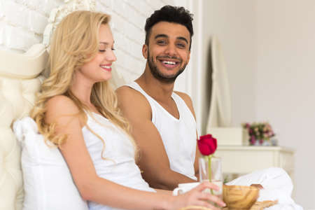 Young Couple Lying In Bed Eat Breakfast Morning With Red Rose Flower, Happy Smile Hispanic Man And Woman Lovers In Bedroom