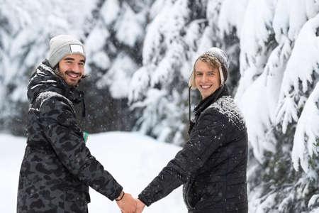 Junger Mann Paar Walking im Schnee Wald im Freien Männer Hände halten Winter-Kiefer Woods